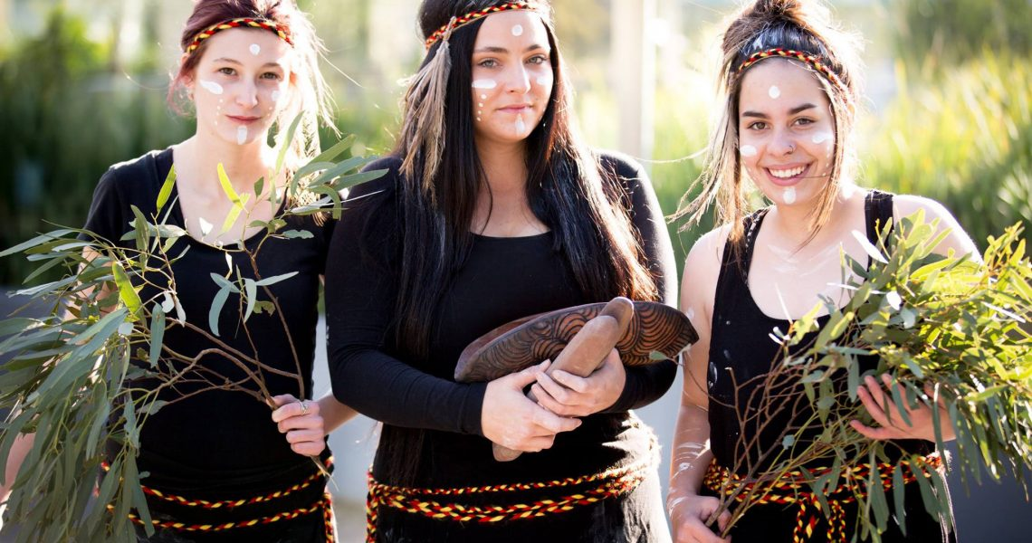 Three young women dancers painted up holding gum leaves