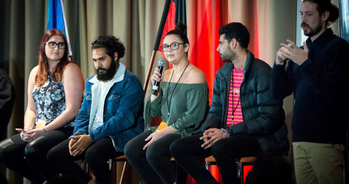 three young people talking on a panel