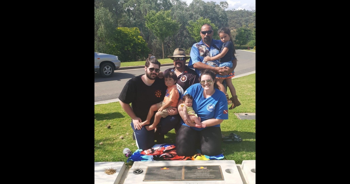 four adults and three children pose in front of a cement grave.